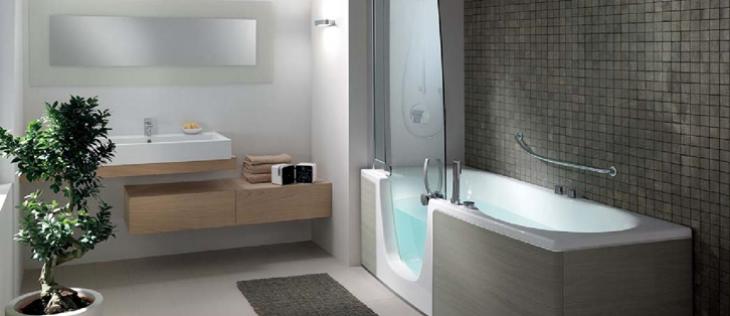 Salle d'eau avec baignoire à porte et lavabo bas.